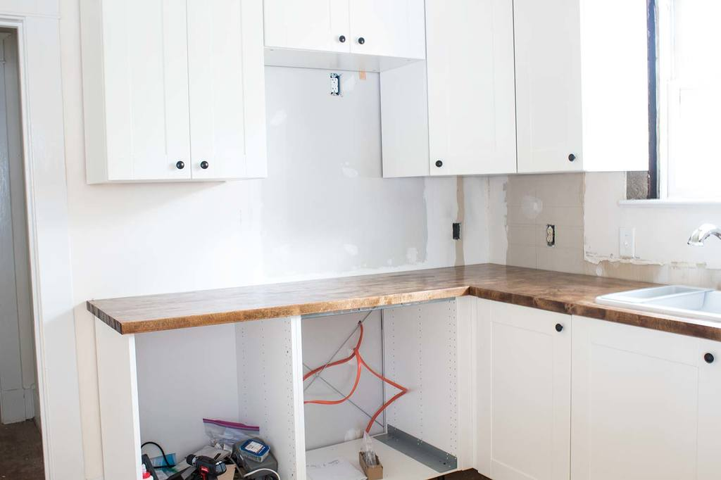 All the details of how I secured my Menards butcherblock countertops to my Ikea cabinets during my complete kitchen remodel. #AButterflyHouse #Kitchens #Countertops #DIY #DIYProjects #HomeImprovement #Butcherblock