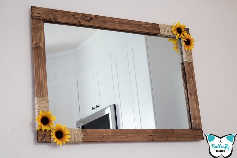 Need some simple wall decor? Take a look at this DIY Farmhouse Sunflower Mirror! Full tutorial shows you how to make a mirror frame out of scrap wood, dollar store sunflowers, and twine. #AButterflyHouse #FarmhouseDecor #Farmhouse #Twine #ScrapWoodProjects #DIY #DIYProjects #Kitchen #Mirror #DIYDecor #DollarStoreCrafts
