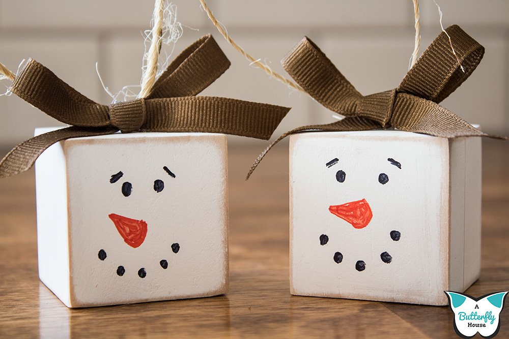 These super cute DIY snowman block ornaments are an easy craft to make and will look great on your Christmas tree! Full tutorial shows you step by step how to complete the project! #AButterflyHouse #DIY #DIYCrafts #DIYProjects #ChristmasCrafts #ChristmasDecor #DIYOrnaments #DIYChristmasOrnaments
