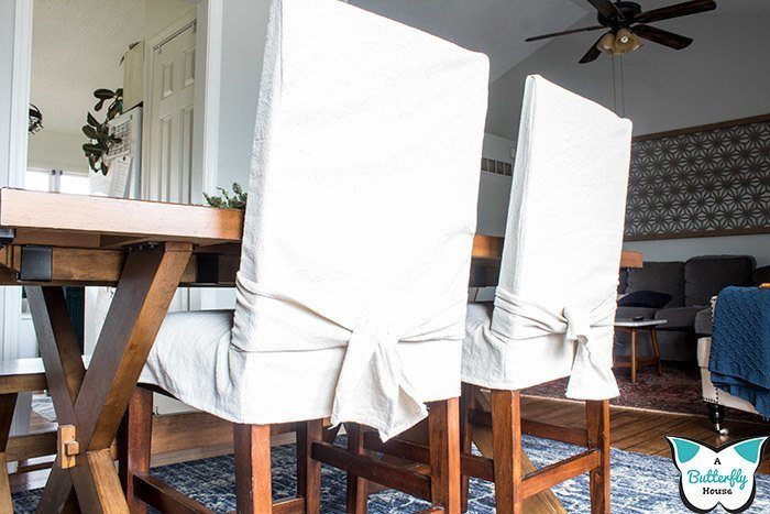 Sew slipcovers for your dining chairs and barstools with this easy sewing tutorial. A great beginner project, these DIY slipcovers are both practical and a great way to improve your sewing skills! #sewing #slipcovers