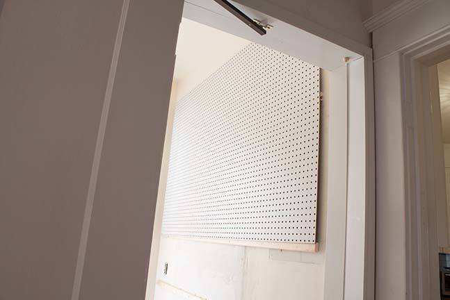 This thorough tutorial shows you exactly how to build a DIY Pegboard Wall in your laundry room, craft room, or garage! This framed pegboard project is done in a weekend and looks fantastic! #organization #homeimprovement