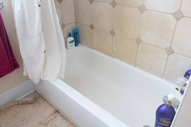 Learn how to refinish a bathtub with this detailed tutorial! Includes everything you need to successfully paint your bathtub and tile, including how to replace the drain, repair chips, and prep for painting! #Homeimprovement #DIY