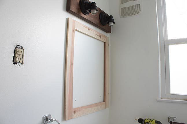 Learn how to frame a mirror - even one with clips - in this detailed tutorial! Easy and affordable method shows you exactly how to frame the bathroom mirror. #DIY #HomeImprovement