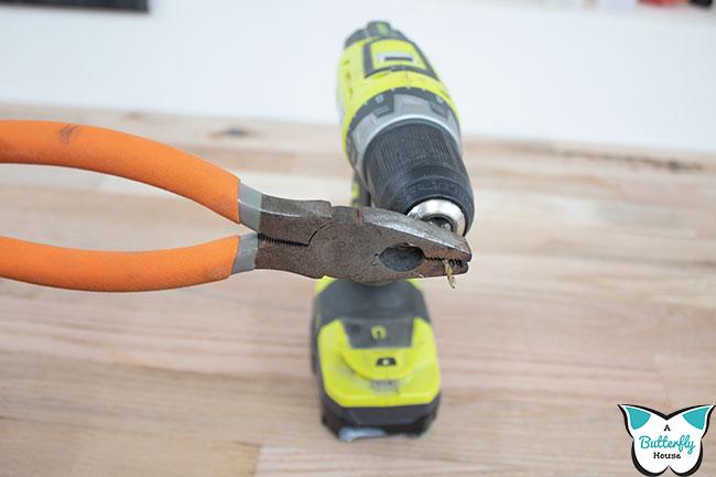 Pliers gripping bit in drill